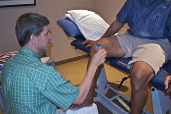 Steve Carling, physical therapist, performs ASTYM therapy on a patient