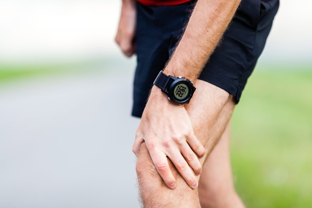 A runner holding his knee in pain.