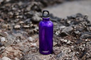 A purple water bottle on rocks in the Arizona desert