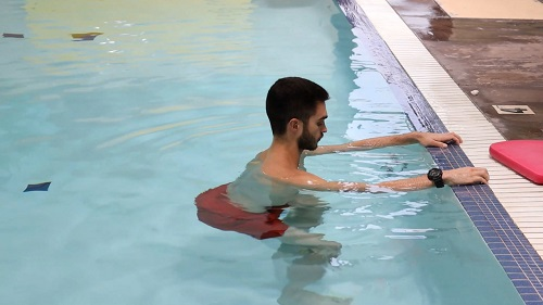 A demonstration of the squat in the pool, while holding onto the edge