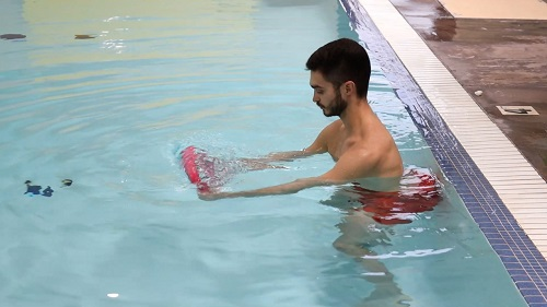 The kickboard being used in the pool for a push and pull exercise