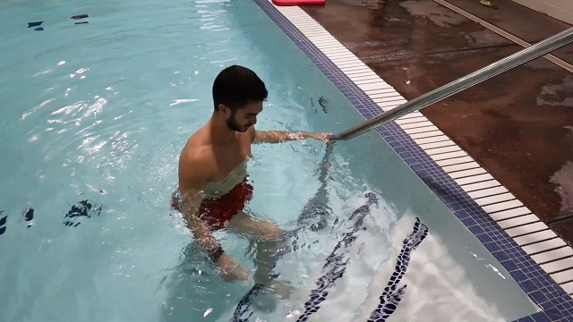 A demonstration of a step up exercise done on a pool step.