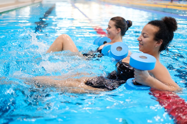 Two ladies in the pool performing aqua therapy.