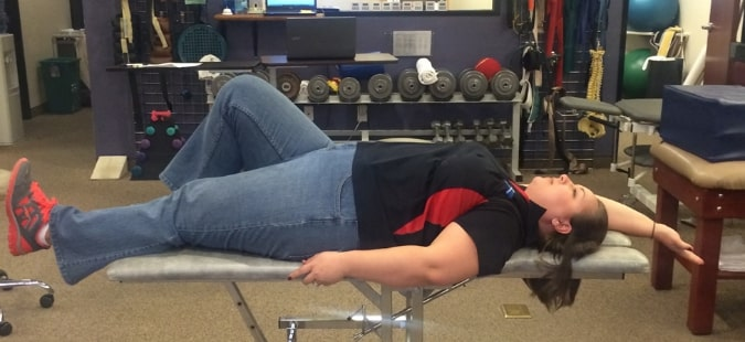 A physical therapy tech performing the opposite arm leg stretch