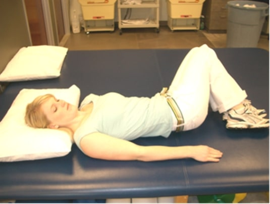 A lady demonstrates the supine trunk rotation for middle back pain.