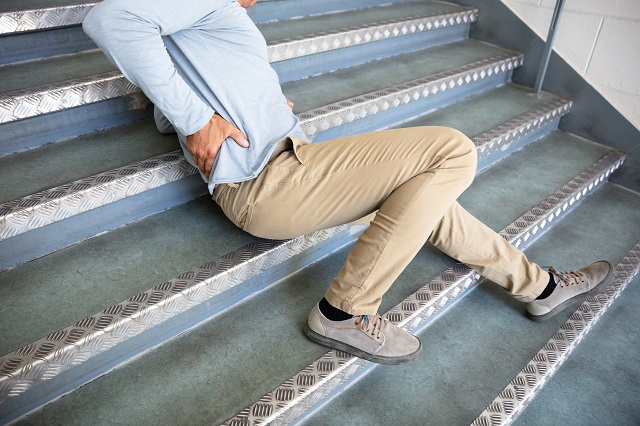 An older man falling and hitting his hip on the stairs.
