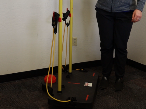 Standing perpendicular to the balance board.