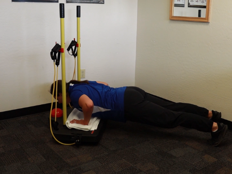 Bottom position of a pushup using the balance board.