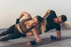 Two adults performing the side plank / bridge exercise from the McGill big three exercise program.