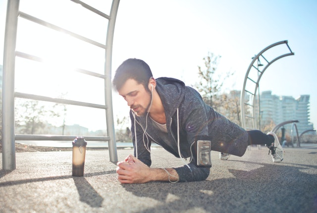 A man performing prone planks for core strength in the park.