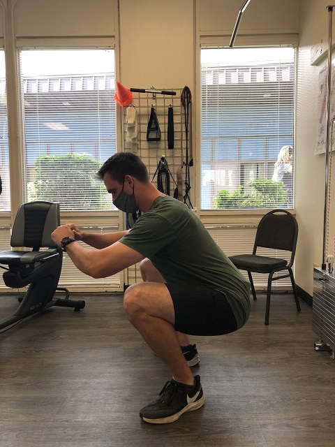 Side view of the air squat bottom position.