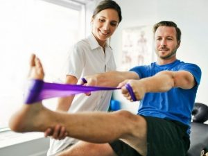 A physical therapist working with a patient on an ankle injury.