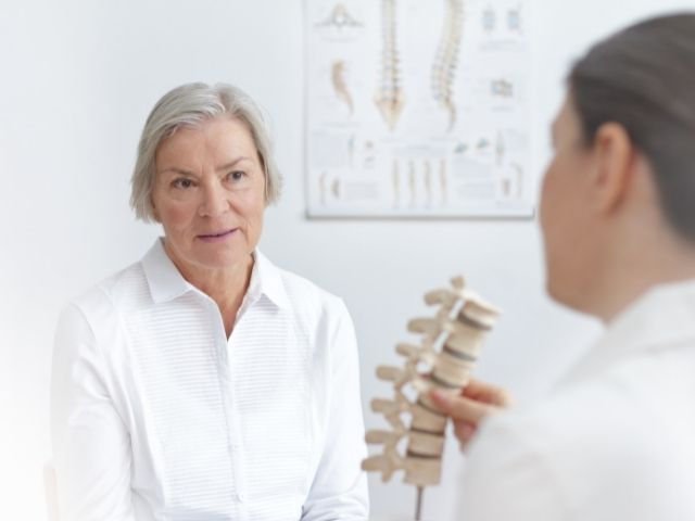 A physical therapist discussing spinal stenosis with a female patient.